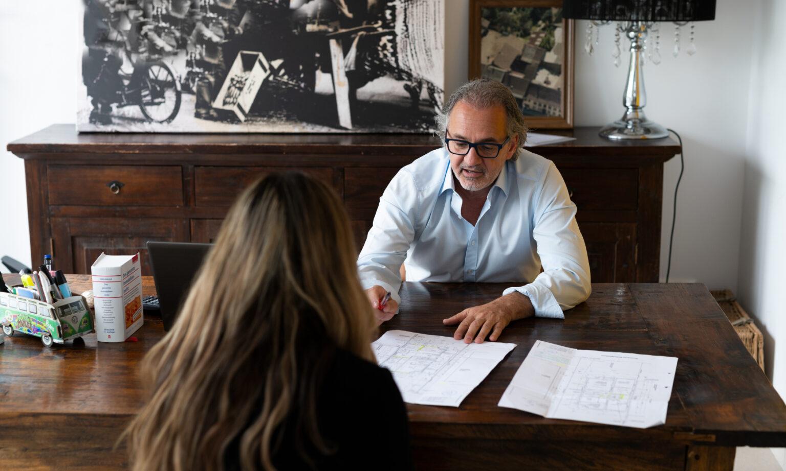 Immobilienmakler im Kundengespräch am Schreibtisch mit Grundrissen